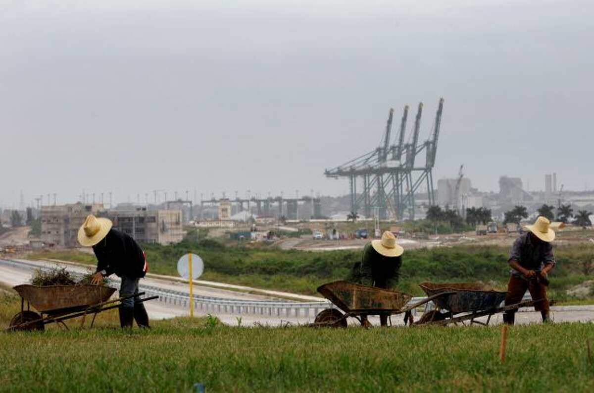 FILE - In this Nov. 6, 2013, file photo, workers landscape the area near a new port under construction in Mariel, Cuba. Cuban authorities are on the verge of enacting a new foreign investment law considered one of the most vital building blocks of President Raul Castro's effort to reform the country's struggling economy. (AP Photo/Franklin Reyes, File)