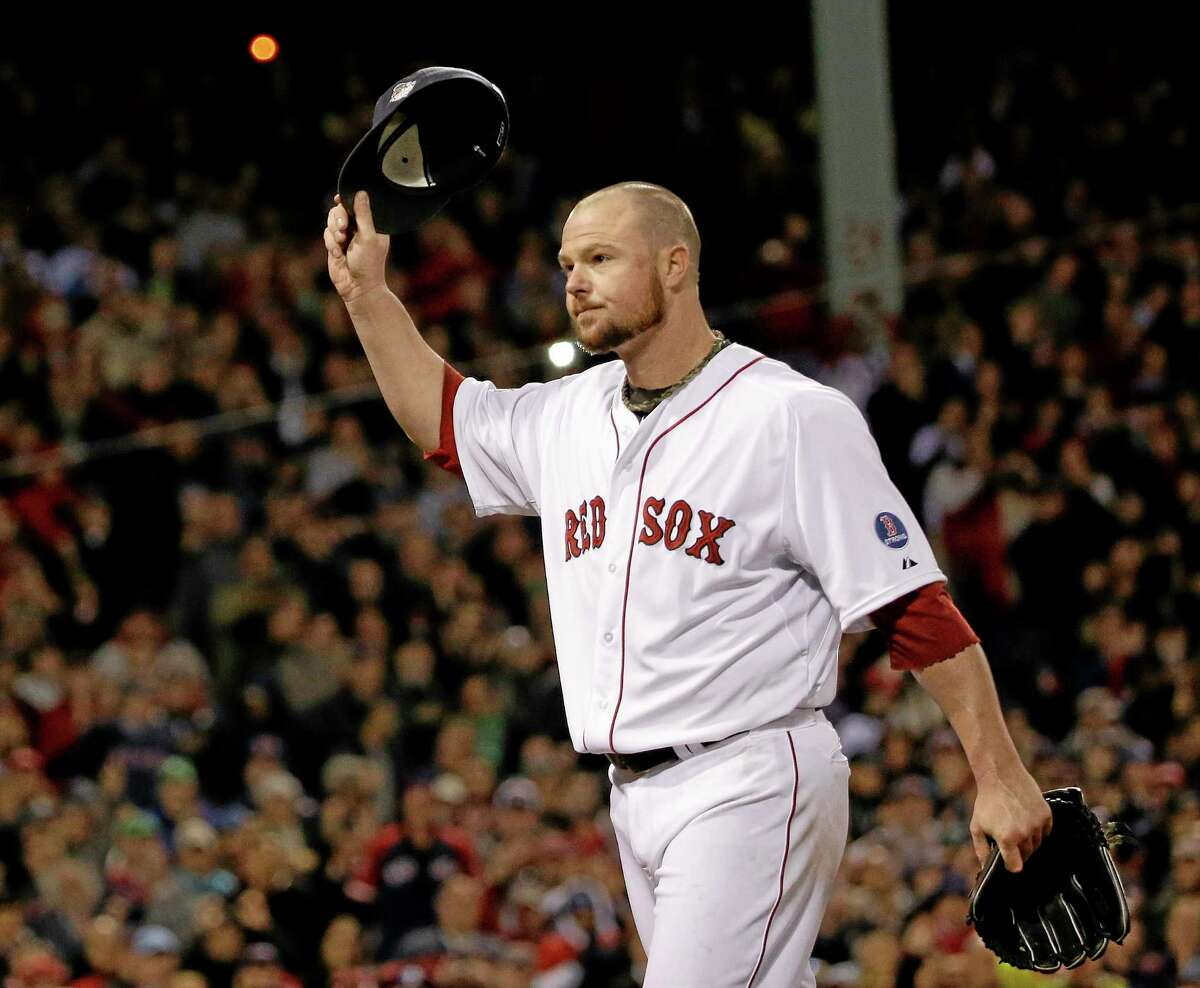 Boston Red Sox starting pitcher Jon Lester acknowledges the crowd as he leaves the game during the eighth inning of Game 1 of baseball's World Series against the St. Louis Cardinals Wednesday, Oct. 23, 2013, in Boston. (AP Photo/David J. Phillip)
