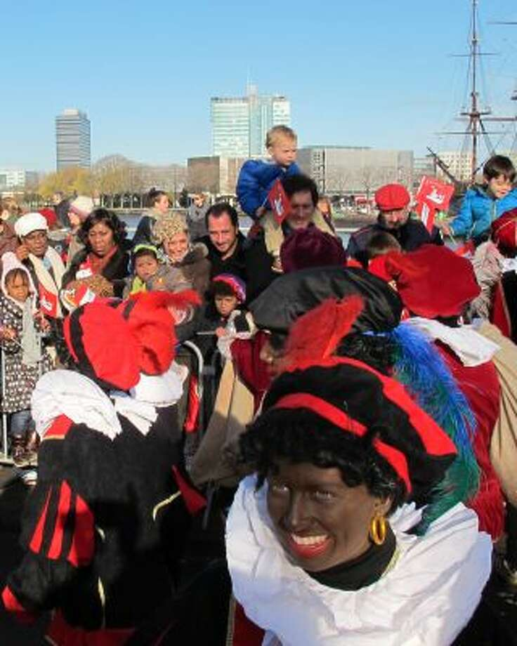 "In this Nov. 18, 2012 file photo persons dressed as ""Zwarte Piet"" or ""Black Pete"" attend a parade after St. Nicholas, or Sinterklaas, arrived by boat in Amsterdam, Netherlands. Photo: AP / AP"