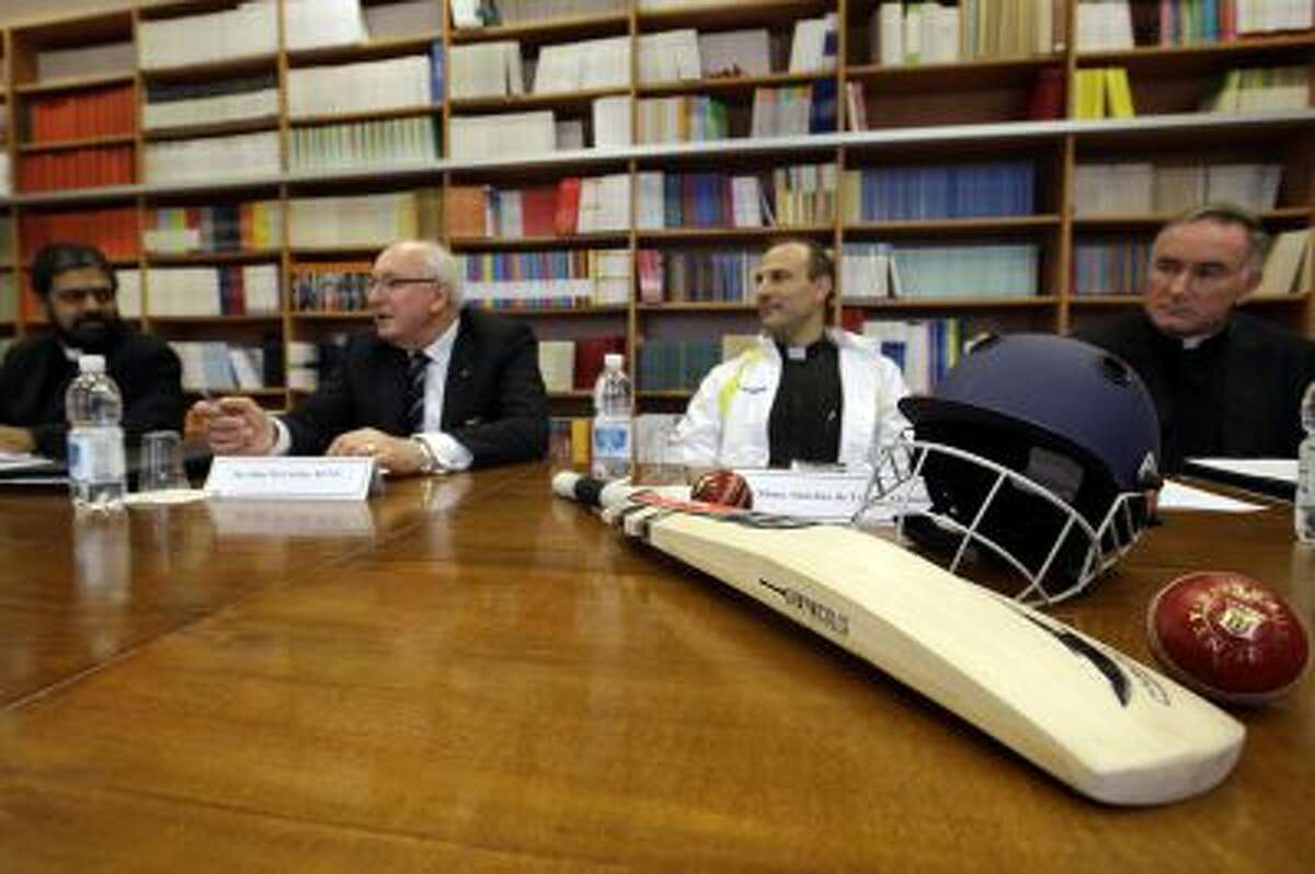 From left, Father Theodore Mascarenhas, Australian Ambassador to the Holy See John McCarthy, Monsignor Sanchez de Toca y Alameda, undersecretary of the Pontifical Council for Culture, and Father Eamon O' Higgins meet the journalists as cricket equipment is displayed on a table at the Vatican on Oct. 22,.