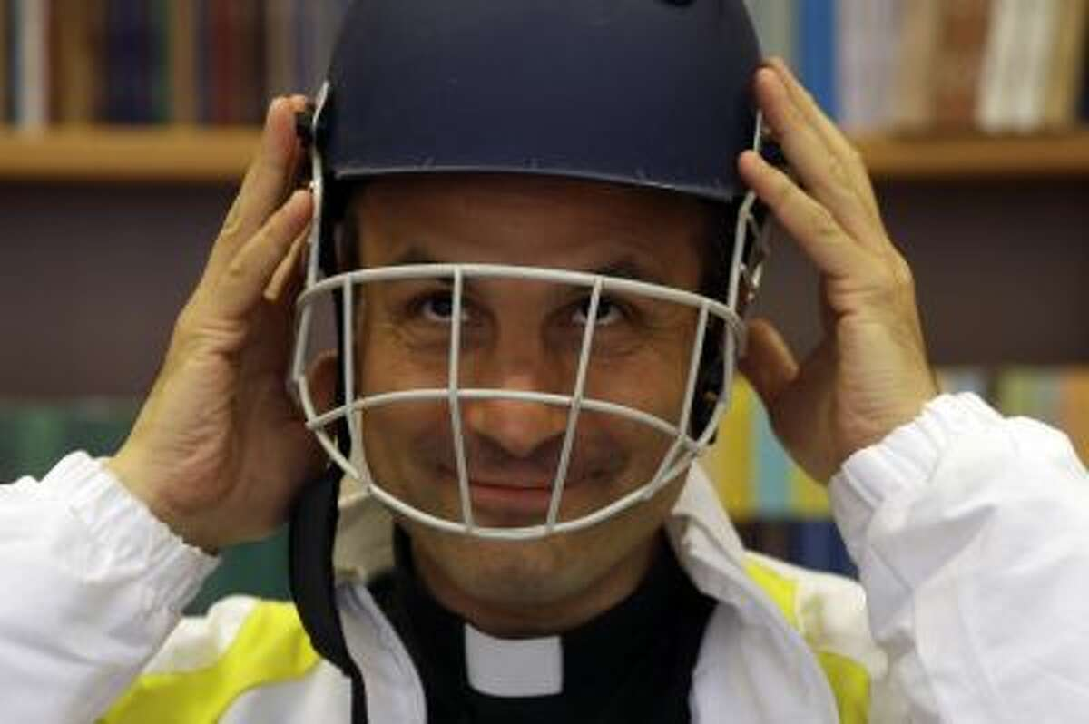 Monsignor Sanchez de Toca y Alameda, undersecretary of the Pontifical Council for Culture, wears a cricket helmet during the presentation of the Vatican cricket club.
