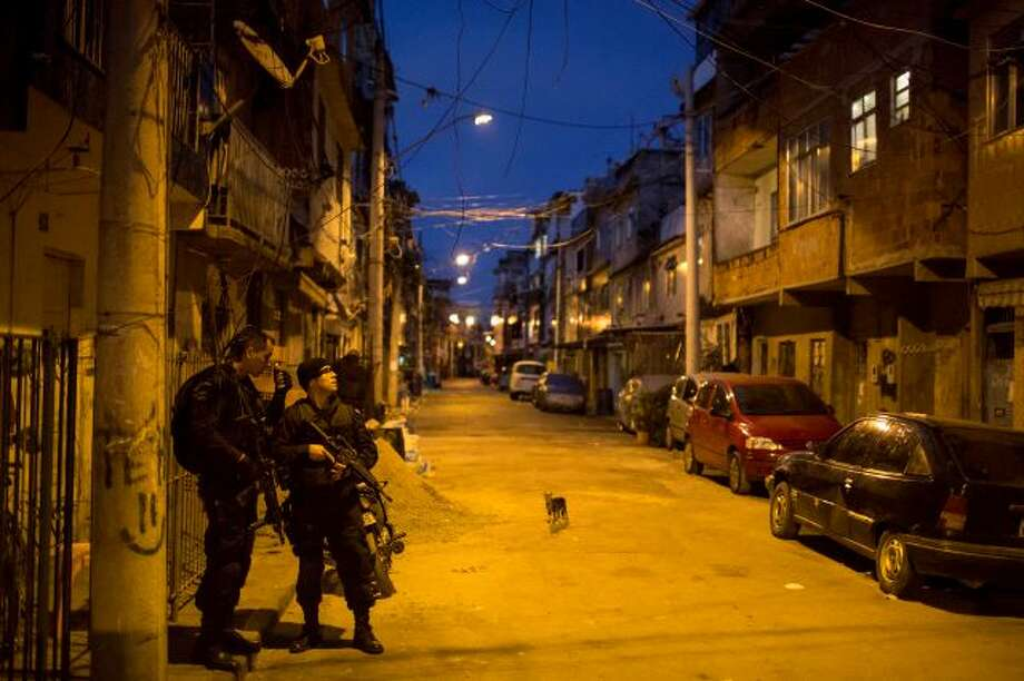 """Special operations battalion Police officers take position during an operation to occupy the Nova Holanda, part of the Mare slum complex in Rio de Janeiro, Brazil, Sunday, March 30, 2014. The Mare complex of slums, home to about 130,000 people and located near the international airport, is the latest area targeted for the government's """"pacification"""" program, which sees officers move in, push out drug gangs and set up permanent police posts. (AP Photo/Felipe Dana) Photo: AP / AP"""