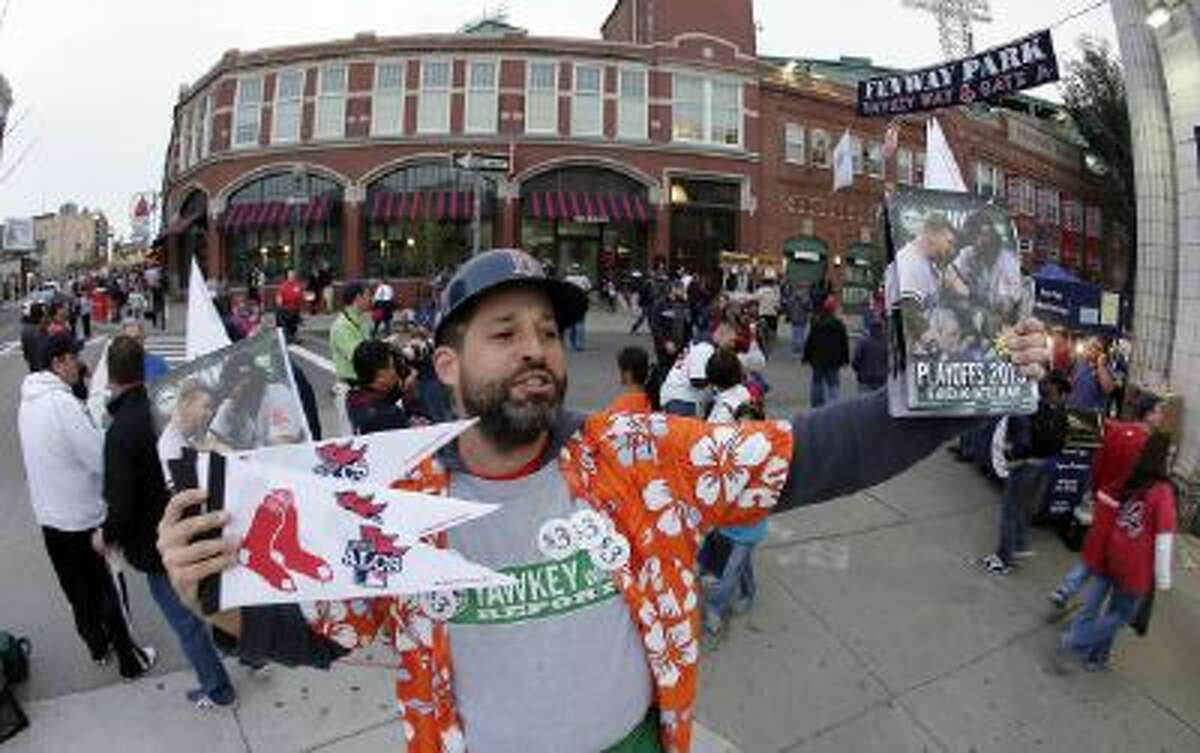 Tim Lampa hawks programs and Boston Red Sox pennants outside Fenway Park before Game 6 of the American League Championship Series between the Red Sox and the Detroit Tigers.