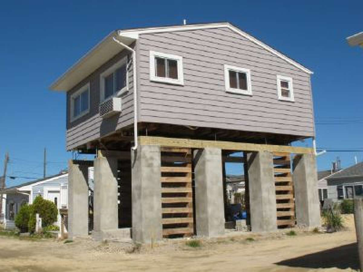 This Sept. 24, 2013 photo shows a house in Toms River, N.J., in the process of being elevated to comply with new federal flood insurance regulations.