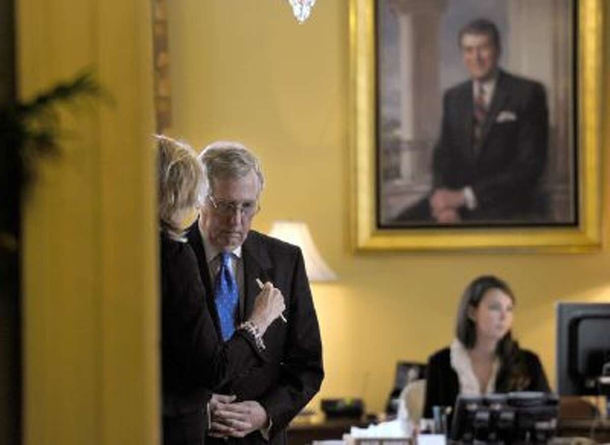In this Oct. 9, 2013, file photo Senate Minority Leader Mitch McConnell of Kentucky talks to an unidentified person in his office before a closed-door meeting of Senate Republicans on Capitol Hill in Washington.