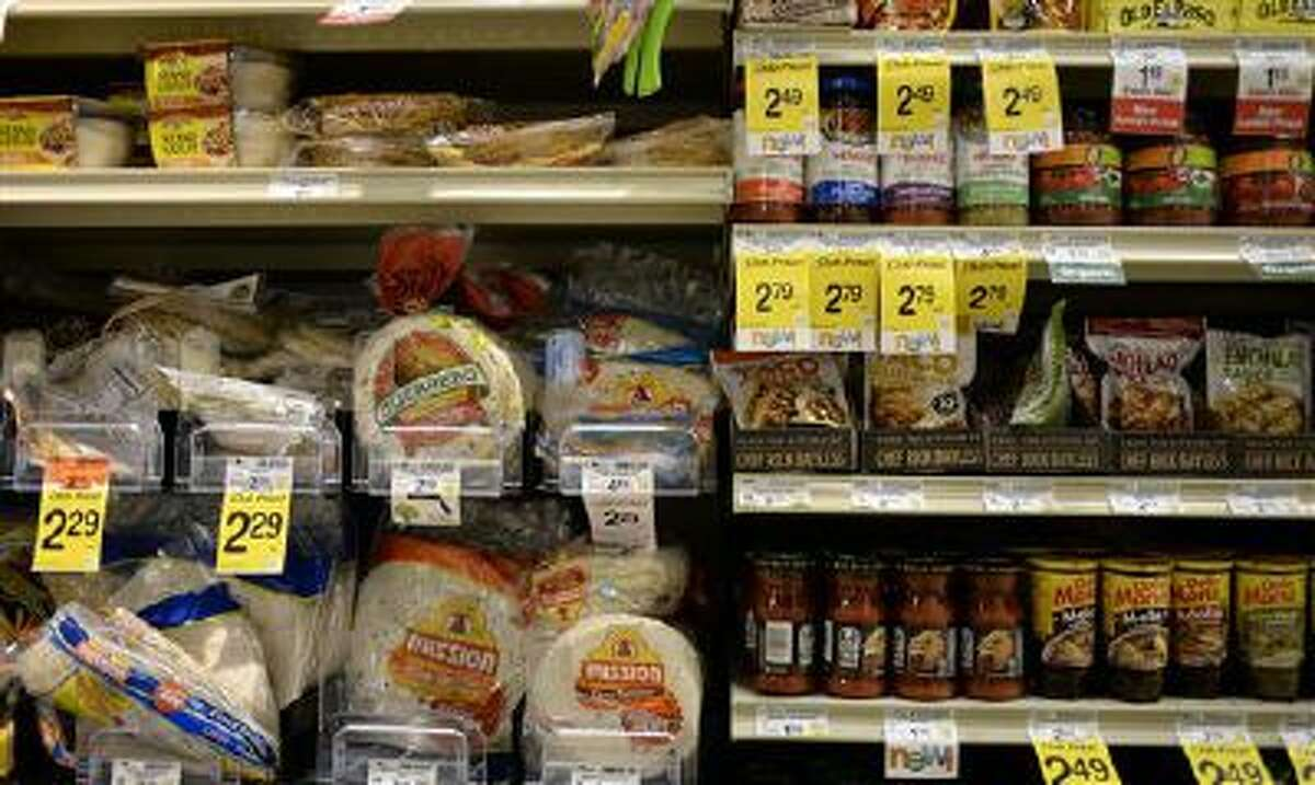 Tortillas and other items are seen in the International food aisle of a grocery store Wednesday, Oct. 16, 2013 in Washington. These days, tortillas outsell burger and hot dog buns; sales of tortilla chips trump potato chips; and tacos and burritos have become so ubiquitously ?American,? most people don?t even consider them ethnic.