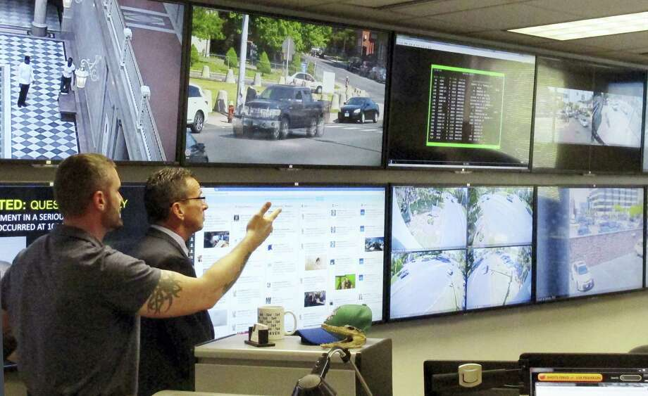 In this Friday, May 20, 2016 photo, Hartford police Sgt. Johnmichael O'Hare, left, shows Connecticut Gov. Dannel P. Malloy the police department's Real-Time Crime and Data Intelligence Center in Hartford, Conn. Staff at the center analyze data from surveillance cameras, gunshot detectors, license plate scanners and other sources. Such facilities are proliferating nationwide with the expanded use of surveillance technology, raising some concerns from civil liberties advocates. (AP Photo/Dave Collins) Photo: AP / Copyright 2016 The Associated Press. All rights reserved. This material may not be published, broadcast, rewritten or redistribu