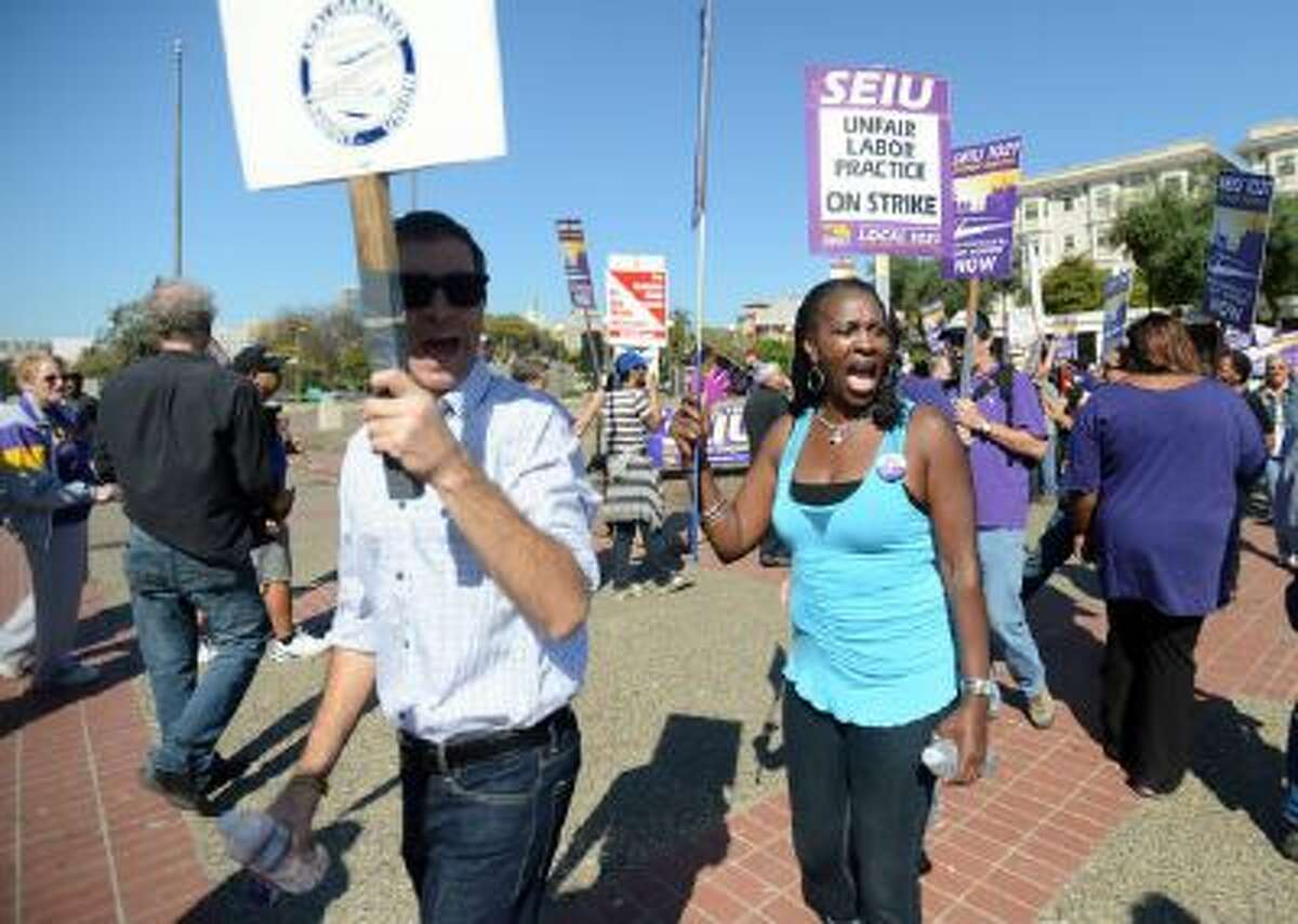 Union members walk the picket line during a noontime rally outside of the Lake Merritt BART station in Oakland, Calif., on Friday, Oct. 18, 2013.