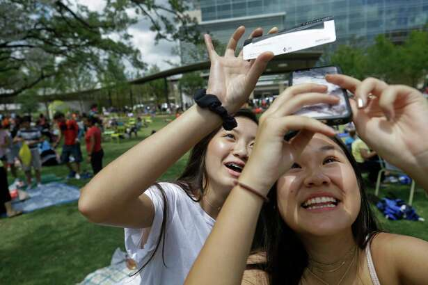 Emily Do, 15, left, and Tiffany Bui, 16, right, try to take a photo through a solar filter of the eclipse at Levy Park, 3801 Eastside St., Monday, Aug. 21, 2017, in Houston. The event at the park was sponsored by the Levy Park Conservancy and the Lunar Planetary Institute.