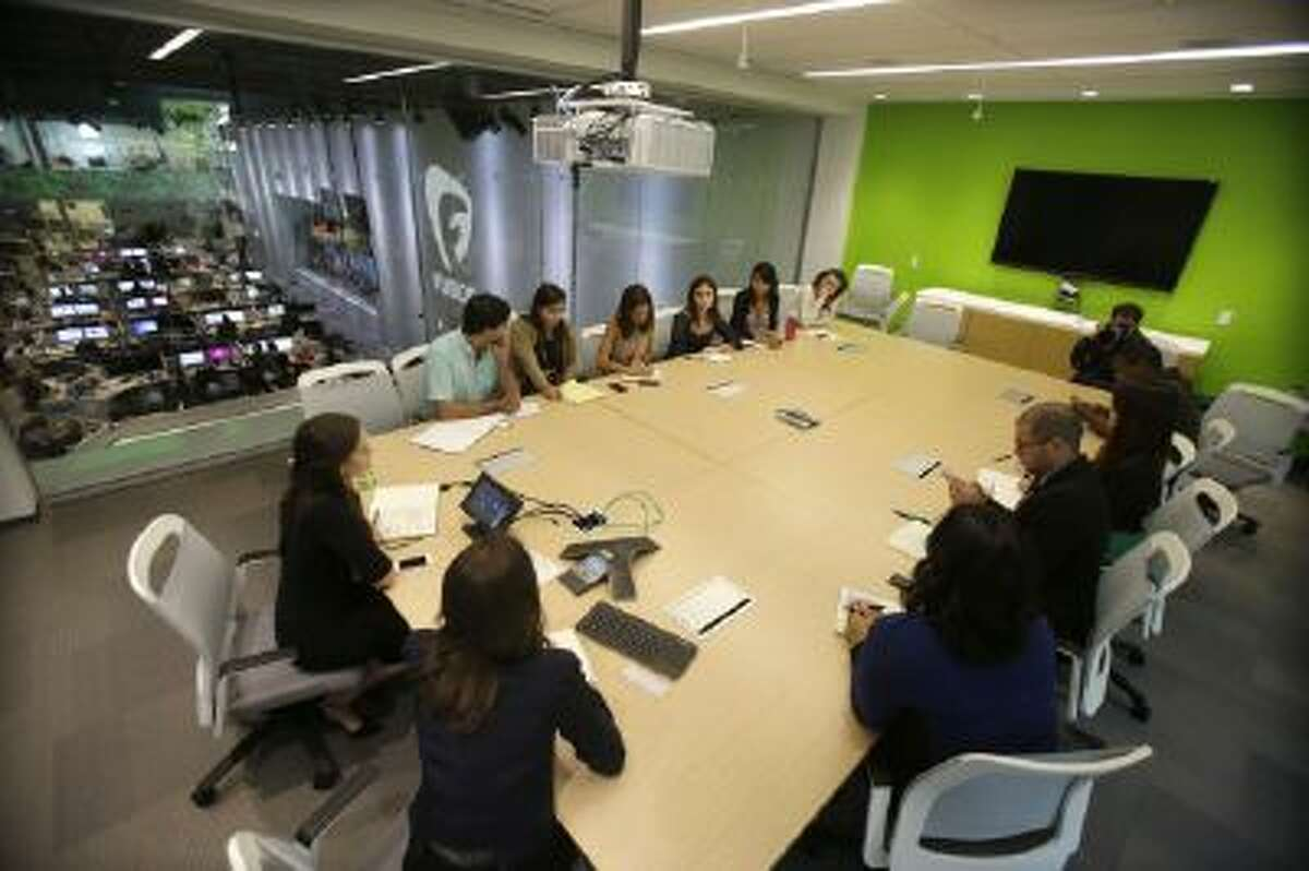 """In this Monday, Oct. 14, 2013 photo Alicia Menendez, foreground, host of the """"Alicia Menendez Tonight"""" show on Fusion, an English-language television network targeting millennial Hispanics, holds an editorial meeting with her production team at the network's offices in Doral, Fla."""