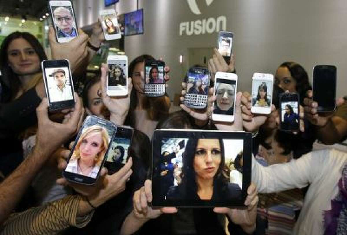 """In this Monday, Oct. 14, 2013 photo Alicia Menendez, center foreground, host of the """"Alicia Menendez Tonight"""" show on Fusion, an English-language television network targeting millennial Hispanics, holds up a """"selfie"""" with her production team as they pose for a photo in Doral, Fla."""