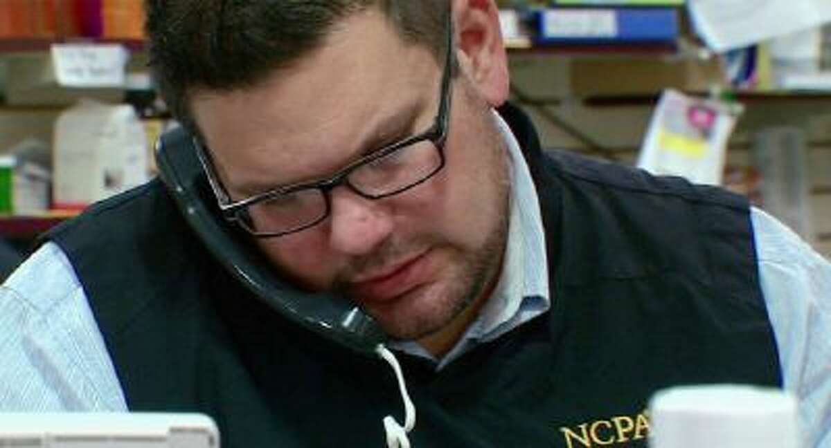 This photo from video taken Oct. 9, 2013, shows Tim Davis on the phone of his pharmacy in New Brighton, Pa. Davis uses several apps and three wearable devices to track his physical activity, vitals and calorie intake.