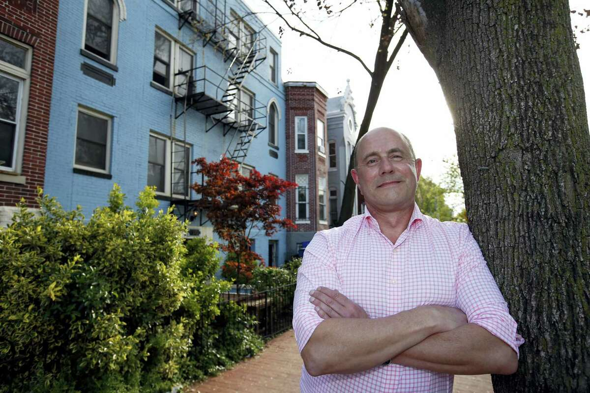 In this Tuesday, April 19, 2016, photo, Jim Phillips poses for a picture in front of the building in which he owns and rents out one of the units, in Washington. Phillips owns three properties, two of which he rents at a monthly positive cash flow of $300 to $400 relative to his ownership expenses. (AP Photo/Alex Brandon)