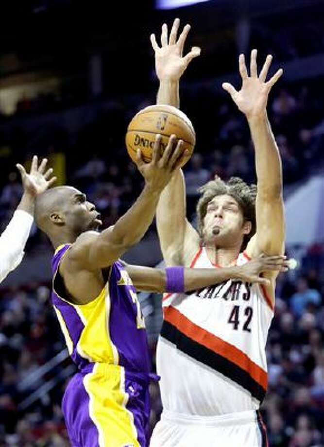 Los Angeles Lakers guard Jodie Meeks, left, goes to the hoop against Portland Trail Blazers center Robin Lopez during the first half of an NBA basketball game in Portland, Ore., Monday, March 3, 2014. (AP Photo/Don Ryan) Photo: AP / AP