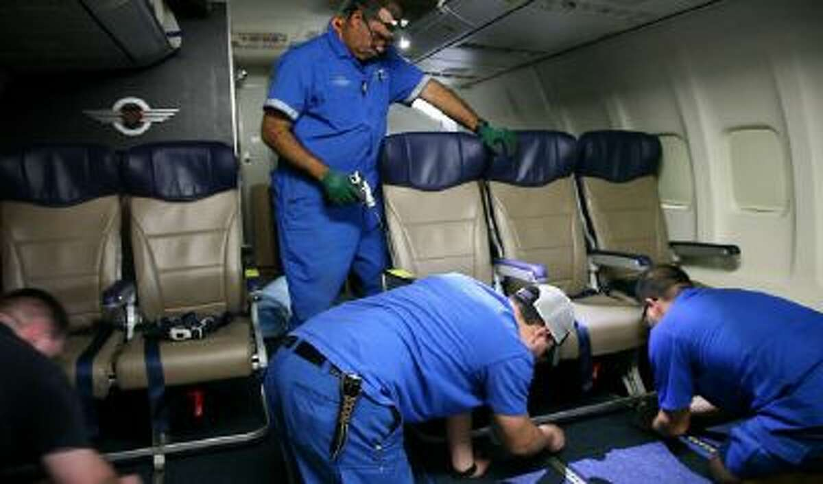 In this Sept. 23, 2013 photo, Southwest Airlines aircraft technicians install newer, skinnier seats on a 737 at the carrier's headquarters in Dallas.
