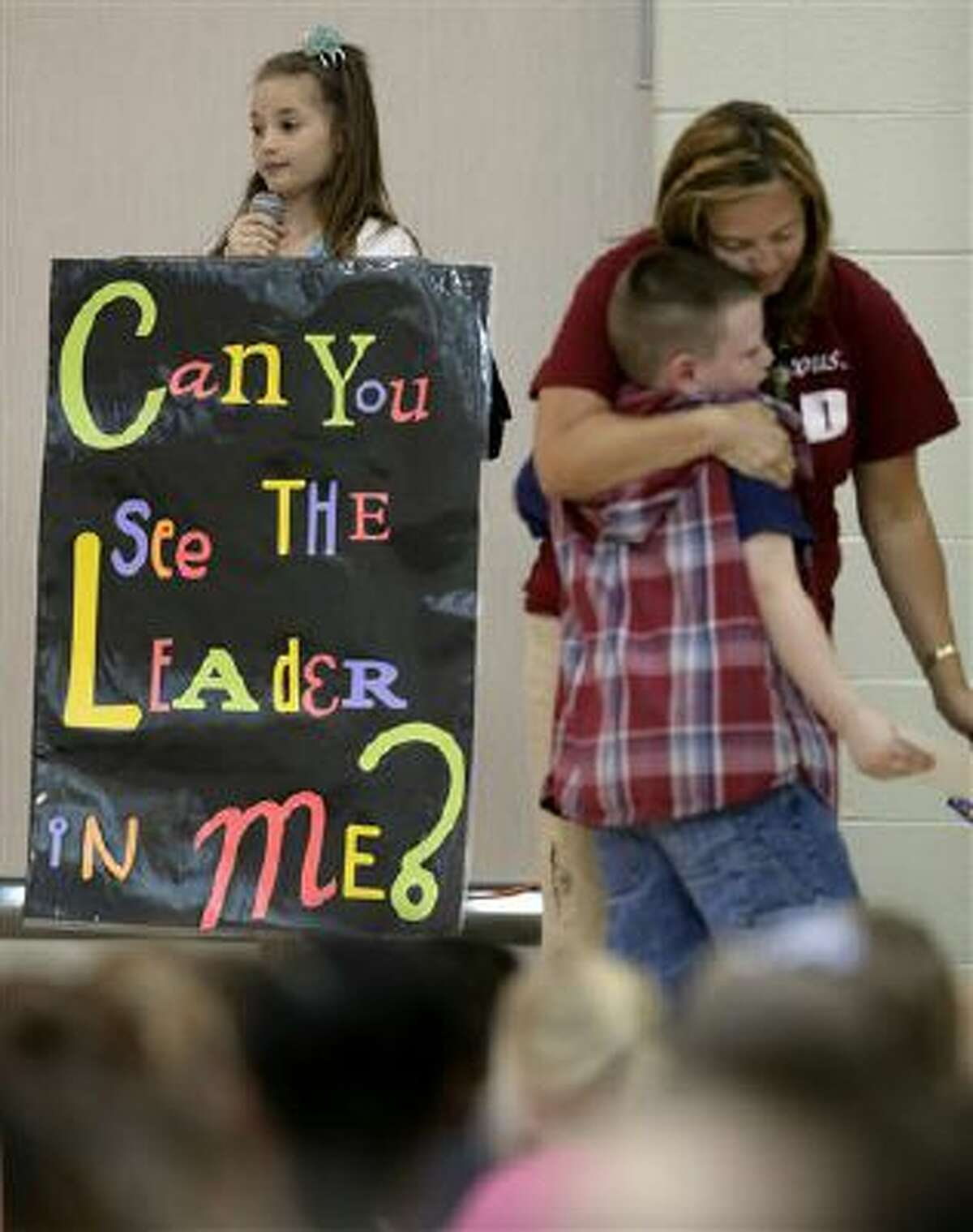 In this photo taken Friday, Sept. 6, 2013, third-grader Jonathan Kent gets a hug from his teacher Mandy Brown after getting an award during a monthly leadership assembly presided over by fourth-grader Anita Bedworth at Indian Trails Elementary school in Independence, Mo.