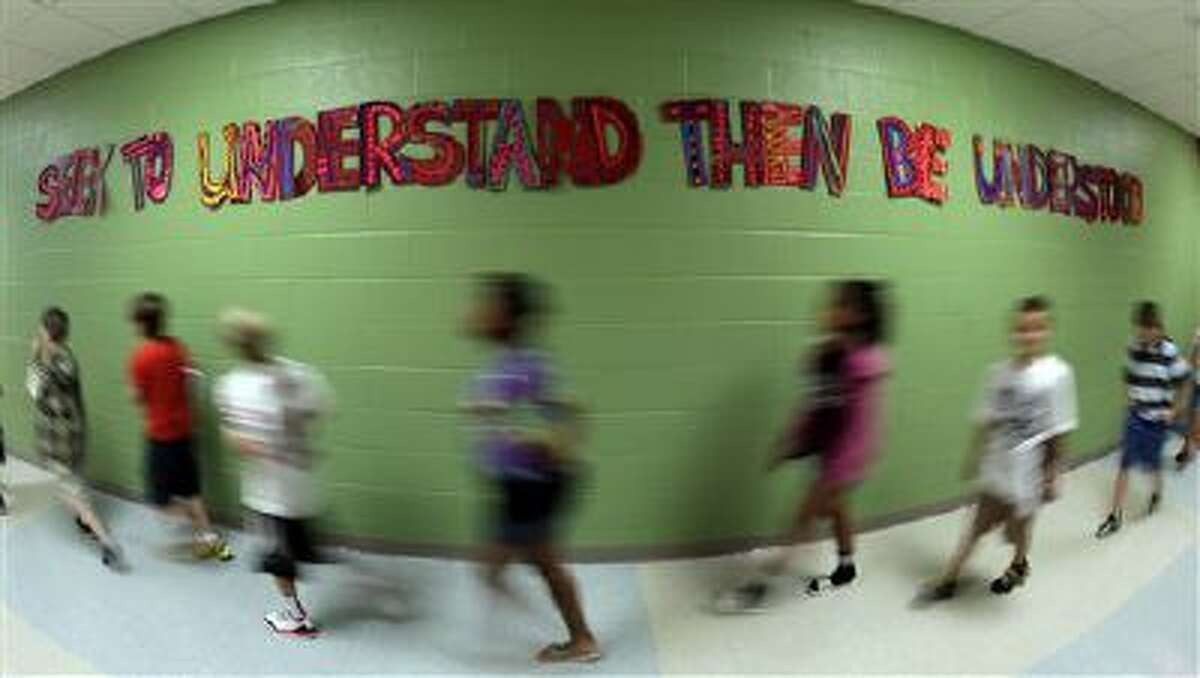 """In this photo taken Friday, Sept. 6, 2013, walk between classes past a sign extolling a leadership principle at Indian Trails Elementary school in Independence, Mo. The school is one of 1,400 nationwide utilizing a program called """"The Leader in Me"""" which is based on the late self-help guru Stephen Covey's best-selling """"The Seven Habits of Highly Effective People."""""""