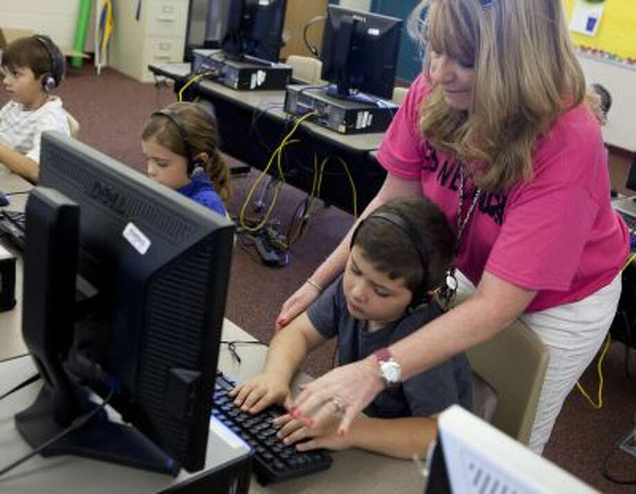 Second-grade teacher Kimberly Blackert helps Cody Simpson with his touch typing assignment on Oct. 11, 2013 at Horseshoe Trails Elementary School in Phoenix, Ariz. Formal keyboarding instruction at the school began this year for second-graders, and is being taught in other schools as early as kindergarten. Photo: For The Washington Post / David Jolkovski
