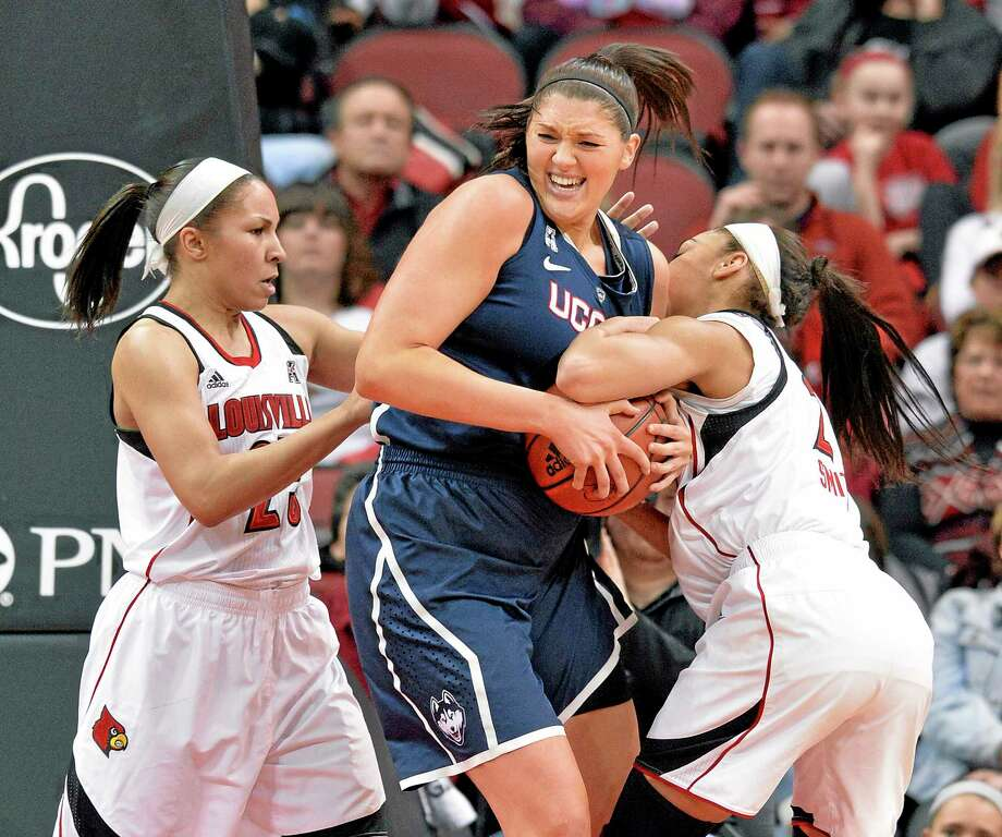 UConn's Stefanie Dolson, center, battles Louisville's Tia Gibbs, left, and Bria Smith for a rebound during the first half Monday. Photo: Timothy D. Easley — The Associated Press  / FR43398 AP