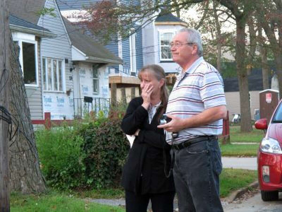 In this Oct. 2, 2013 photo, Sue Sutton, left, fights back tears as she watches her home being demolished, with her husband, Bart, in Union Beach, N.J.