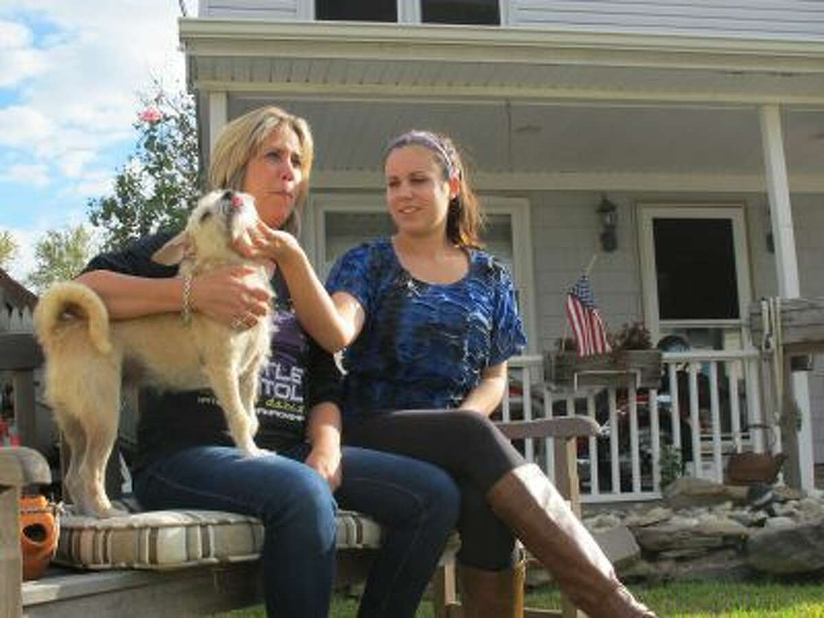 In this Sept,. 26, 2013 photo, In this Sept,. 26, 2013 photo, Simone Dannecker, left, and her daughter Nicole, right, play with their dog on the porch of their Union Beach, N.J. home that the family fixed themselves after Superstorm Sandy.