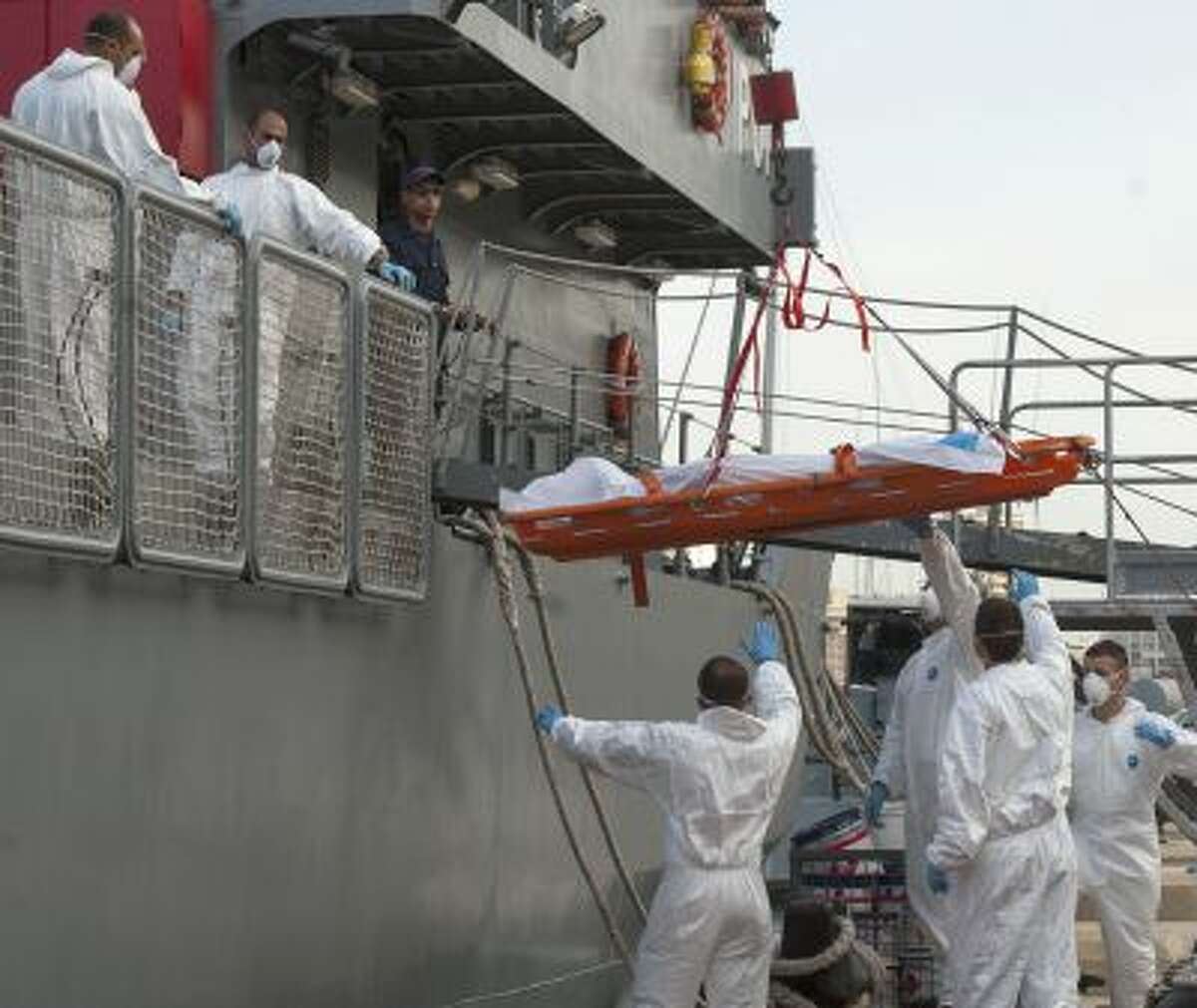 A body is being lowered down from a Maltese Navy ship at the Valletta harbor, Malta, Saturday, Oct. 12, 2013.