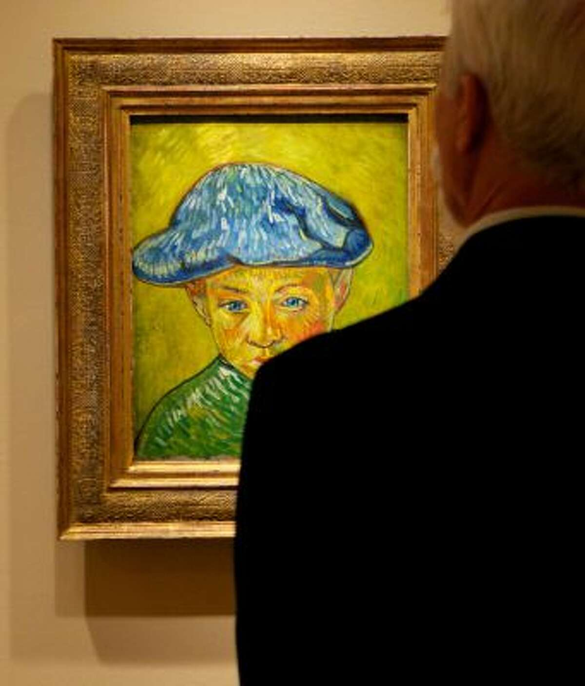 """In this Oct. 8, 2013 photo, a visitor studies Vincent van Gogh's """"Portrait of Camille Roulin,"""" on display at The Phillips Collection in Washington. (AP Photo/Molly Riley)"""