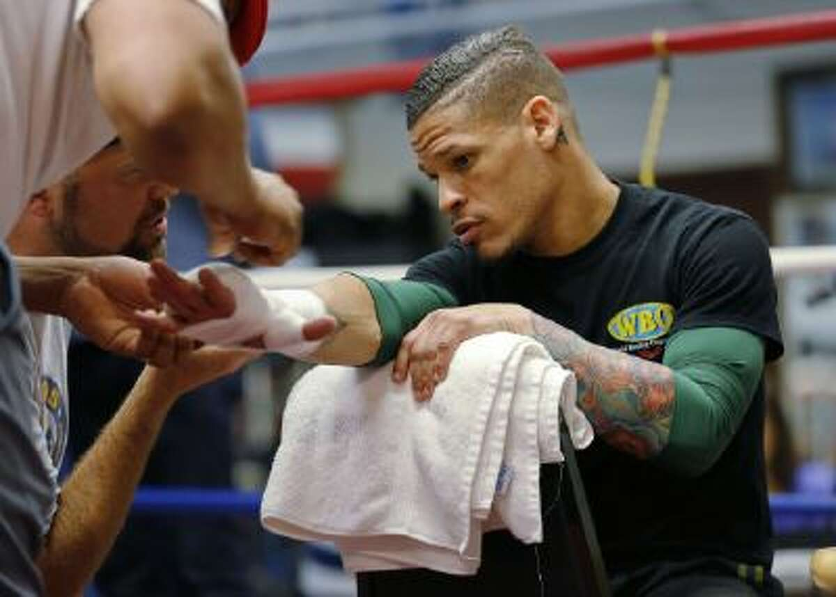 FILE - In this Sept. 24, 2013 file photo, boxer Orlando Cruz has his hands wrapped before a workout at Mendez Boxing Gym, in New York.