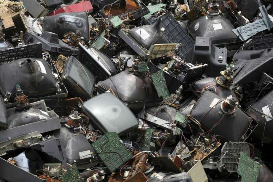 In this photo taken Aug. 26, 2013, discarded television sets pile up in a scrap yard awaiting recycling in Zhuzhou city in south China's Hunan province. China's recycling industry has boomed over the past 20 years. Its manufacturers needed the metal, paper and plastic and Beijing was willing to tolerate the environmental cost. But environmentalists have long complained the industry is poisoning China's air, water and soil. (AP Photo) CHINA OUT Photo: AP / CHINATOPIX