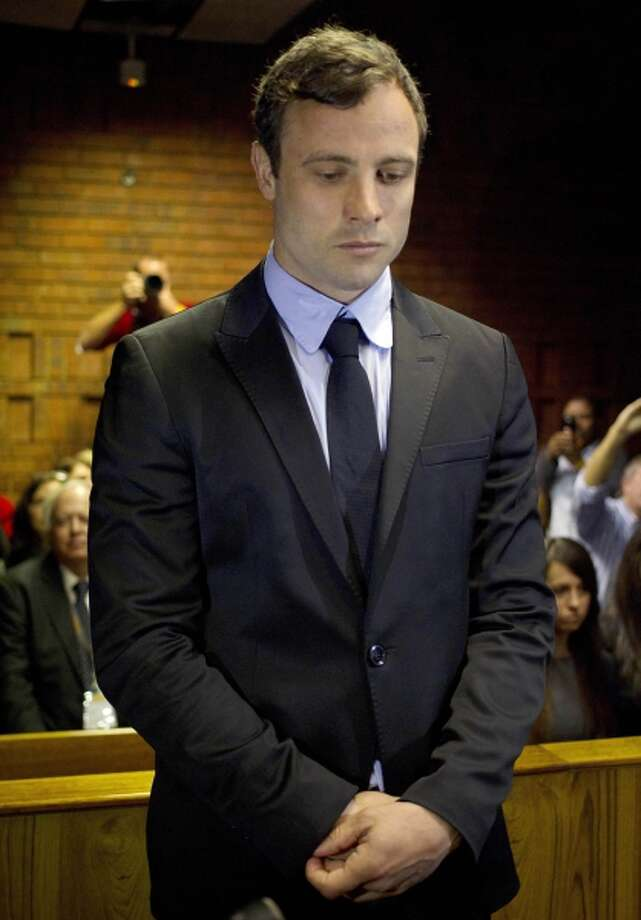 FILE In this file photo taken Monday, Aug. 19, 2013 double-amputee Olympian Oscar Pistorius, at the magistrates court in Pretoria, South Africa, when Pistorius was indicted on charges of murder and illegal possession of ammunition for the shooting death of his girlfriend on Valentine's Day. Oscar Pistorius' lawyers are working with a team of American forensic specialists to help prepare the double-amputee Olympian's defense, and likely counter any evidence given by the nearly 50 police... Photo: AP / AP