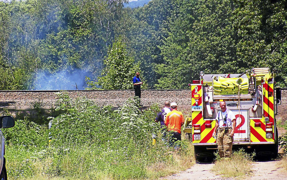 (Wes Duplantier/The New Haven Register)Firefighters from North Haven and Hamden worked for more than an hour Monday to contain a brush fire along the railroad tracks near part of Washington Avenue in North Haven. Photo: Journal Register Co.