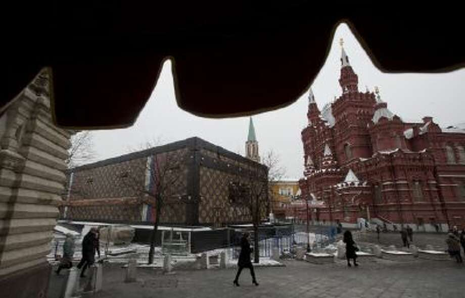 Tourists and visitors pass by a two-story Louis Vuitton suitcase erected at the Red Square in Moscow, Russia, on Nov. 27, 2013.