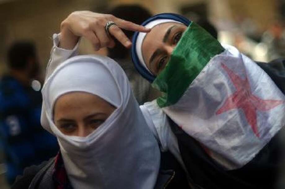 Syrian women pose for a picture during an anti-regime protest in the northern Syrian city of Aleppo on April 13, 2013.