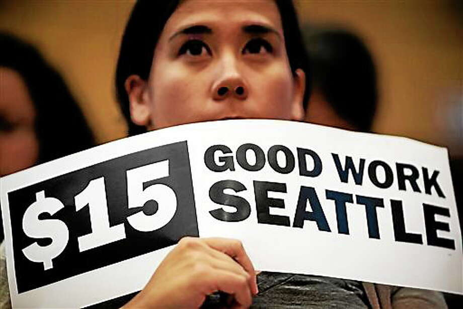 Hoisting signs, supporters showed support for the passage of increasing the minimum wage in the city to $15 for Seattle employers on Monday, June 2, 2014, at City Hall in Seattle. Phased in over the next seven years, Seattle will have the highest minimum wage in America. (AP Photo/seattlepi.com, Jordan Stead) Photo: AP / seattlepi.com