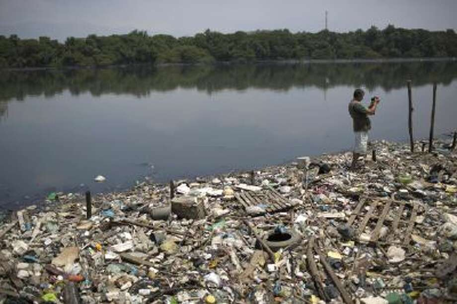 In this Oct. 23, 2013 photo, biologist Mario Moscatelli takes photographs from trash floating on the polluted waters of the Canal do Fundao in Rio de Janeiro, Brazil. Moscatelli, who oversees the reforestation of mangrove forests along the bay, said he fears that even if the bay is cleaned up, the state will let it deteriorate after all the athletes have gone home