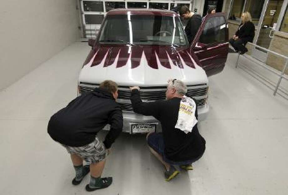 In this Oct. 17, 2013 photo, Rich Vahle, right, and his son, Lane, pop the hood of a customized 1993 Chevrolet Silverado pickup truck at Poage Auto Plaza in Quincy, Ill. The truck once belonged to Rich's father, Dan, who died of cancer in 1997, and was returned to the family.