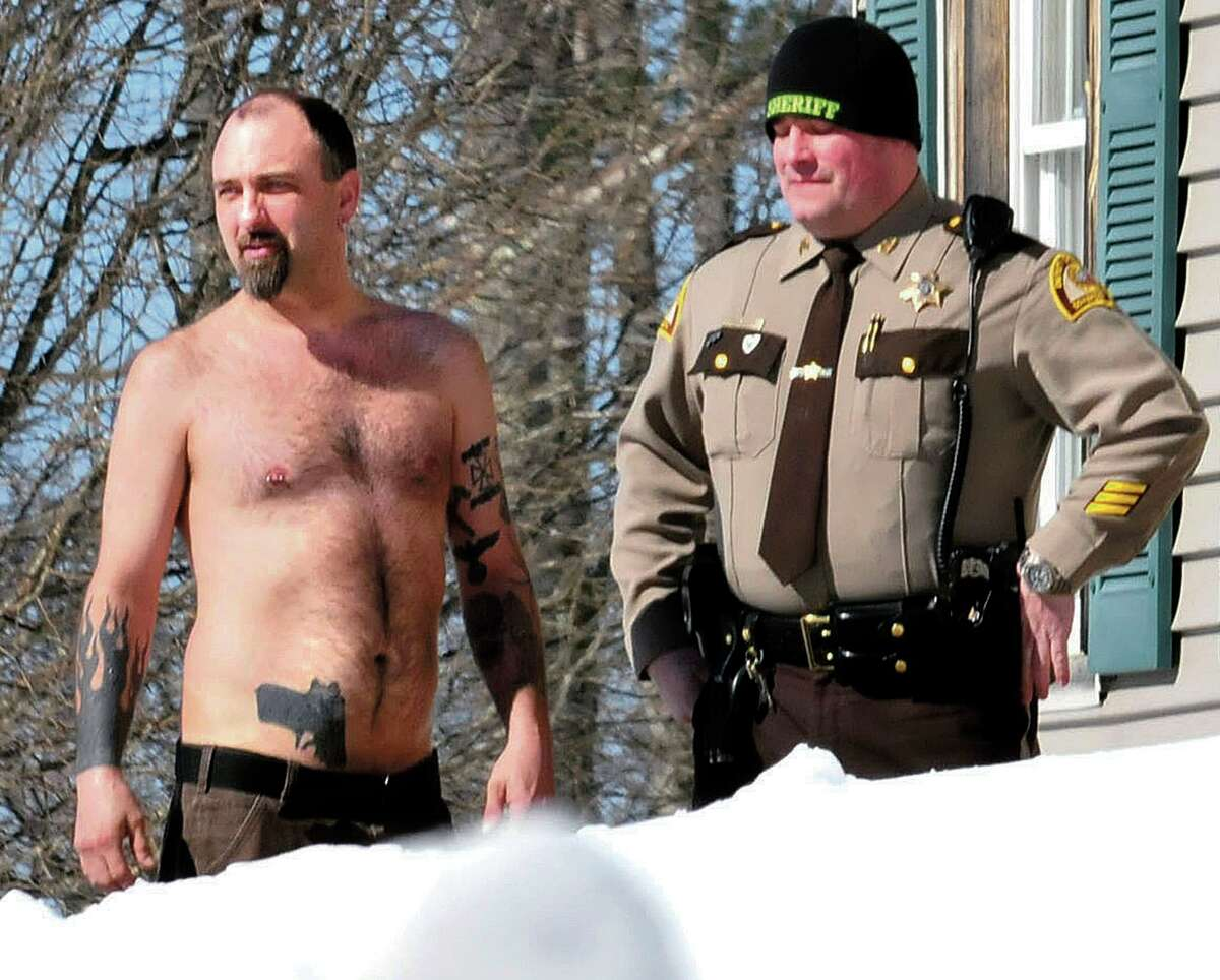 In this March 18 file photo, Michael Smith, left, bearing a realistic-looking tattoo of a handgun on his stomach, stands beside a Somerset County Sheriff deputy outside his home in Norridgewock, Maine. (AP Photo/Morning Sentinel, David Leaming, File)