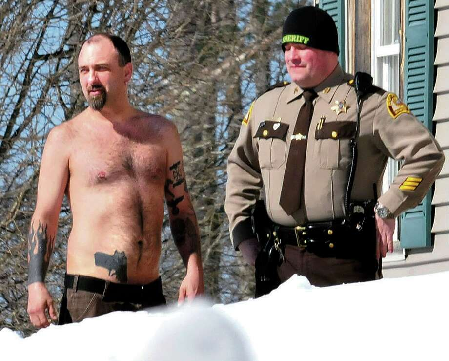 In this March 18 file photo, Michael Smith, left, bearing a realistic-looking tattoo of a handgun on his stomach, stands beside a Somerset County Sheriff deputy outside his home in Norridgewock, Maine. (AP Photo/Morning Sentinel, David Leaming, File) Photo: AP / Morning Sentinel