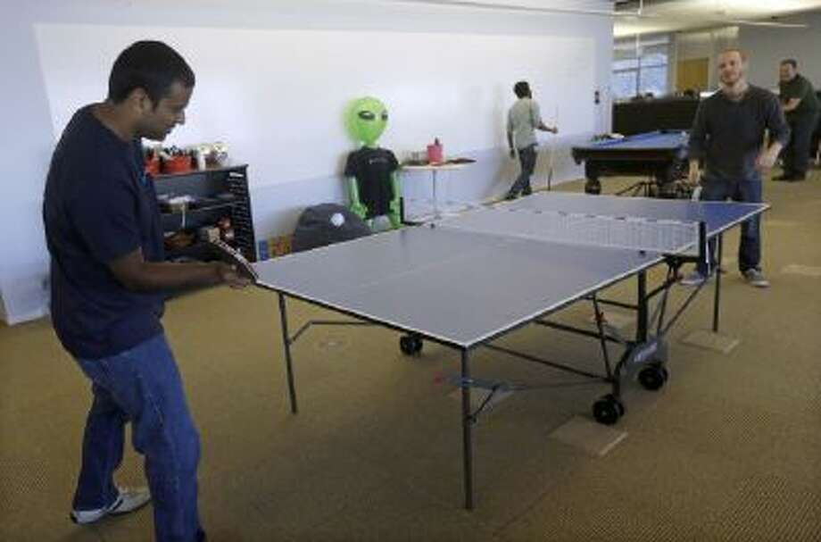 In this Sept. 18, 2013 photo, Pranay Kuruvilla, senior software engineer for Walmartlabs, left, plays ping pong with Benjamin Pellow, principal software engineer, at the Walmart.com office in San Bruno, Calif.