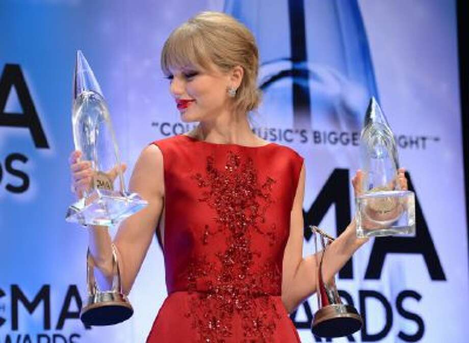 """Taylor Swift poses backstage with her awards for musical event of the year and music video of the year for """"Highway Don't Care,"""" and the pinnacle award at the 47th annual CMA Awards at Bridgestone Arena on Wednesday, Nov. 6, 2013, in Nashville, Tenn. The fourth award was from a previous year."""