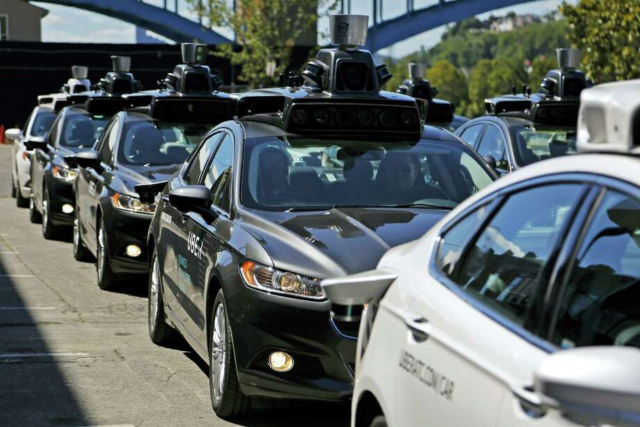 FILE - In this Monday, Sept. 12, 2016, file photo, a group of self-driving Uber vehicles position themselves to take journalists on rides during a media preview at Uber's Advanced Technologies Center in Pittsburgh. U.S. President Donald Trump's economic plans are nothing if not ambitious, including his vision of creating 25 million jobs over 10 years. However, the widespread use of robots and automation by companies has increasingly allowed businesses to operate with fewer workers. For example, Uber is experimenting with self-driving cars, and restaurant chains like Eatsa can now serve lunch and dinner through an automated order-and-payment system, and no cashiers or servers are necessary. (AP Photo/Gene J. Puskar, File) Photo: AP / Copyright 2016 The Associated Press. All rights reserved.