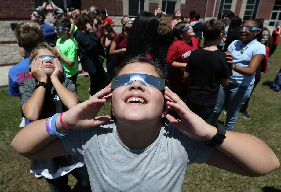 Rogers Middle School 6th grader Evangeline Curless (foreground) and her classmates used eclipse glasses, Monday, Aug. 21, 2017, in Pearland. Rogers' Principal Lakesha Vaugh said that between Pearland ISD and the teachers they were able to purchase about 820 eclipse glasses allowing the entire student body to witness the historic event. Photo: Steve Gonzales, Houston Chronicle / © 2017 Houston Chronicle