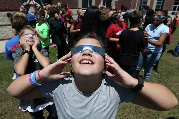 Rogers Middle School 6th grader Evangeline Curless (foreground) and her classmates used eclipse glasses, Monday, Aug. 21, 2017, in Pearland. Rogers' Principal Lakesha Vaugh said that between Pearland ISD and the teachers they were able to purchase about 820 eclipse glasses allowing the entire student body to witness the historic event.