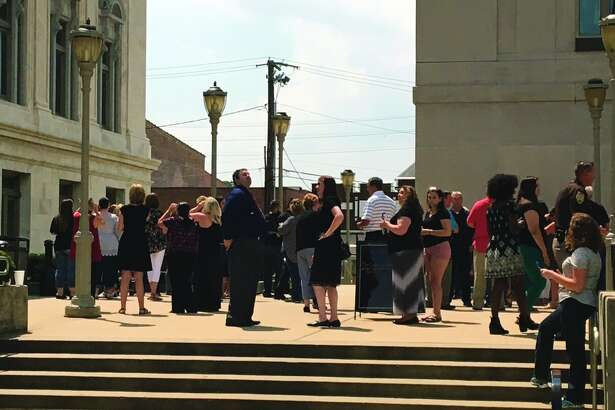 Eclipse watchers gather outside the Madison County Courthouse Monday afternoon.