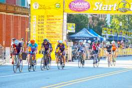 Cyclists pedal through downtown during the Cat 5 race at the eighth edition of TheBank of Edwardsville Rotary Criterium on Saturday. The event featured eight races and four kids races with thousands lining the street.