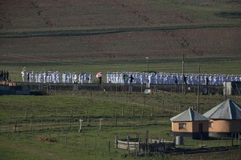 Members of the South African navy line the road from the Mandela family house to his burial site prior to the burial of former South African President Nelson Mandela in his hometown Qunu, South Africa, Sunday Dec. 15, 2013.