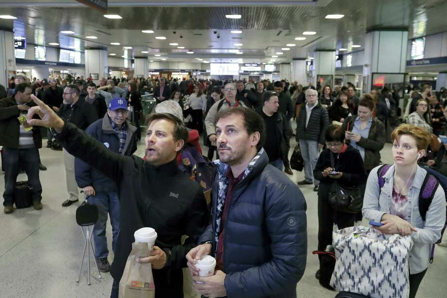 FILE - In this April 3, 2017 file photo, waiting commuters and passengers in New York's Penn Station look up to a train schedule board after delays were created when a train derailed earlier in the day. New Jersey Transit said one of its trains derailed while pulling into the station at a slow speed. The derailment comes a week and a half after an Amtrak train partially derailed as it pulled out of Penn Station. (AP Photo/Mark Lennihan, File) Photo: AP / Copyright 2017 The Associated Press. All rights reserved.