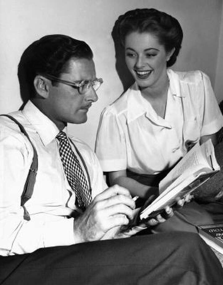 """In this Aug. 25, 1945 photo, Errol Flynn seems to be in a literary mood as, between takes on the set of """"Never Say Goodbye,"""" he reads an amusing passage from a new novel to his leading lady, Eleanor Parker, who appears to enjoy the presentation in Los Angeles."""