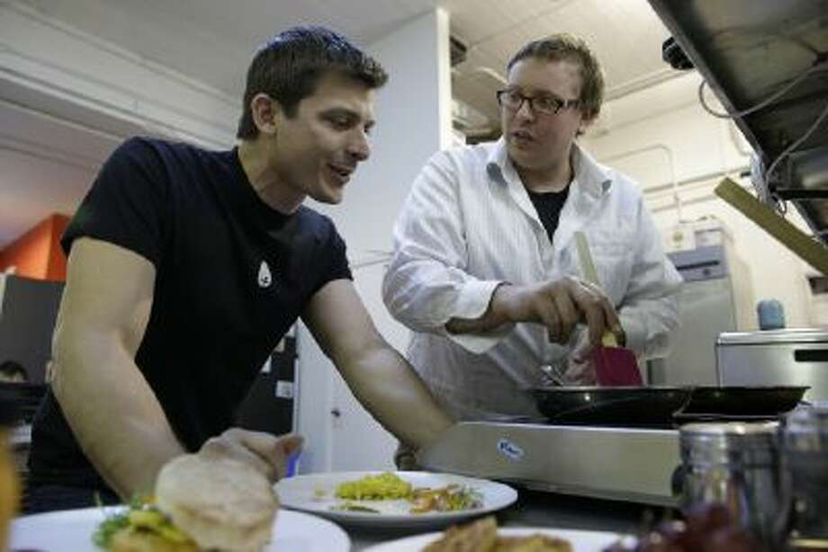 In this photo taken Tuesday, Dec. 3, 2013, CEO Josh Tetrick, left, watches as research and development chef Trevor Niekowal, right, makes a plant-based scrambled egg at Hampton Creek Foods in San Francisco.