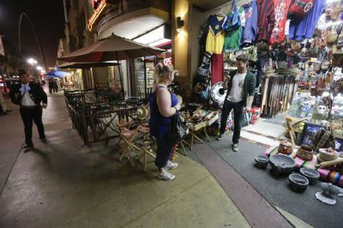 In this Nov. 15, 2013 photo, Amanda Beverly, of Newfoundland, Canada, center, looks over souvenirs with Tijuana tour guide Derrik Chinn as a Mariachi musician passes, left, in Tijuana, Mexico.